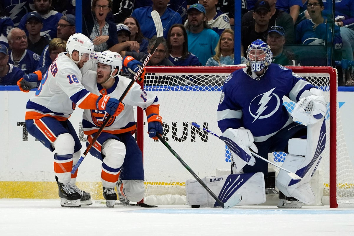 New York Islanders center Mathew Barzal (13) celebrates with left wing Anthony Beauvillier (18) after Barzal scored past Tampa Bay Lightning goaltender Andrei Vasilevskiy (88) during the second period in Game 1 of an NHL hockey Stanley Cup semifinal playoff series Sunday, June 13, 2021, in Tampa, Fla. (AP Photo/Chris O'Meara)