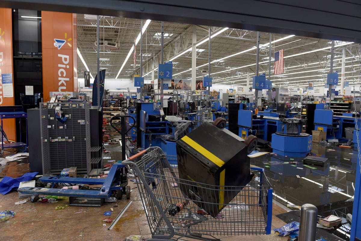 Items litter the ground Wednesday, Oct. 28, 2020, inside a Walmart in Philadelphia that was damaged in last night's protests.(AP Photo/Michael Perez)