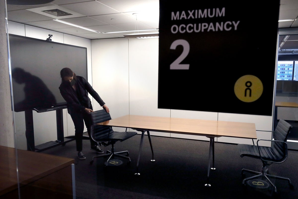In this Thursday, May 7, 2020 photo, Vice President Rachel Zsembery at the design firm Bergmeyer, positions chairs in a conference room with a designated maximum occupancy of two people, at the firm's offices, in Boston. Out of concern for the coronavirus Bergmeyer is restructuring the way its workspace is used, including reinstalling dividers on 85 desks at its Boston office that had been removed over the years. (AP Photo/Steven Senne)
