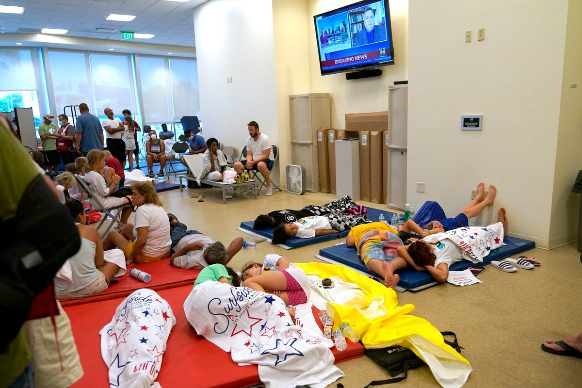 People lie on cots as they wait for news at a family reunification center, after a wing of a 12-story beachfront condo building collapsed, Thursday, June 24, 2021, in the Surfside area of Miami. (AP Photo/Lynne Sladky)