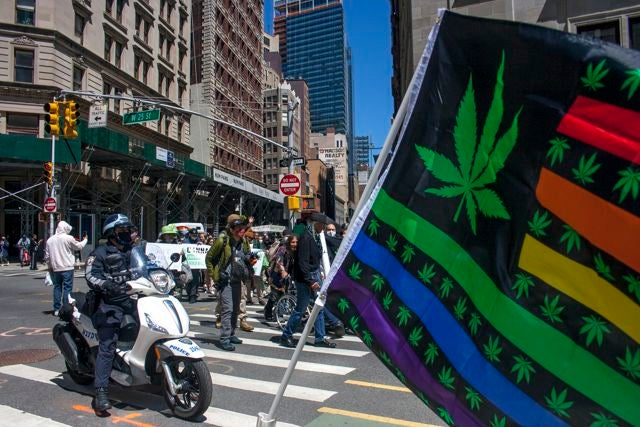 NYPD escorts look on as marchers smoke cannabis along the parade route. (Chloe Aiello/Cheddar)