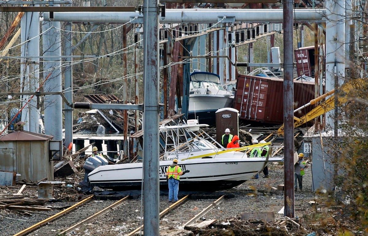 Workers try to clear boats and debris from the New Jersey Transit's Morgan draw bridge after surge from Superstorm Sandy pushed boats and cargo containers onto the train tracks.<i>(AP)</i>