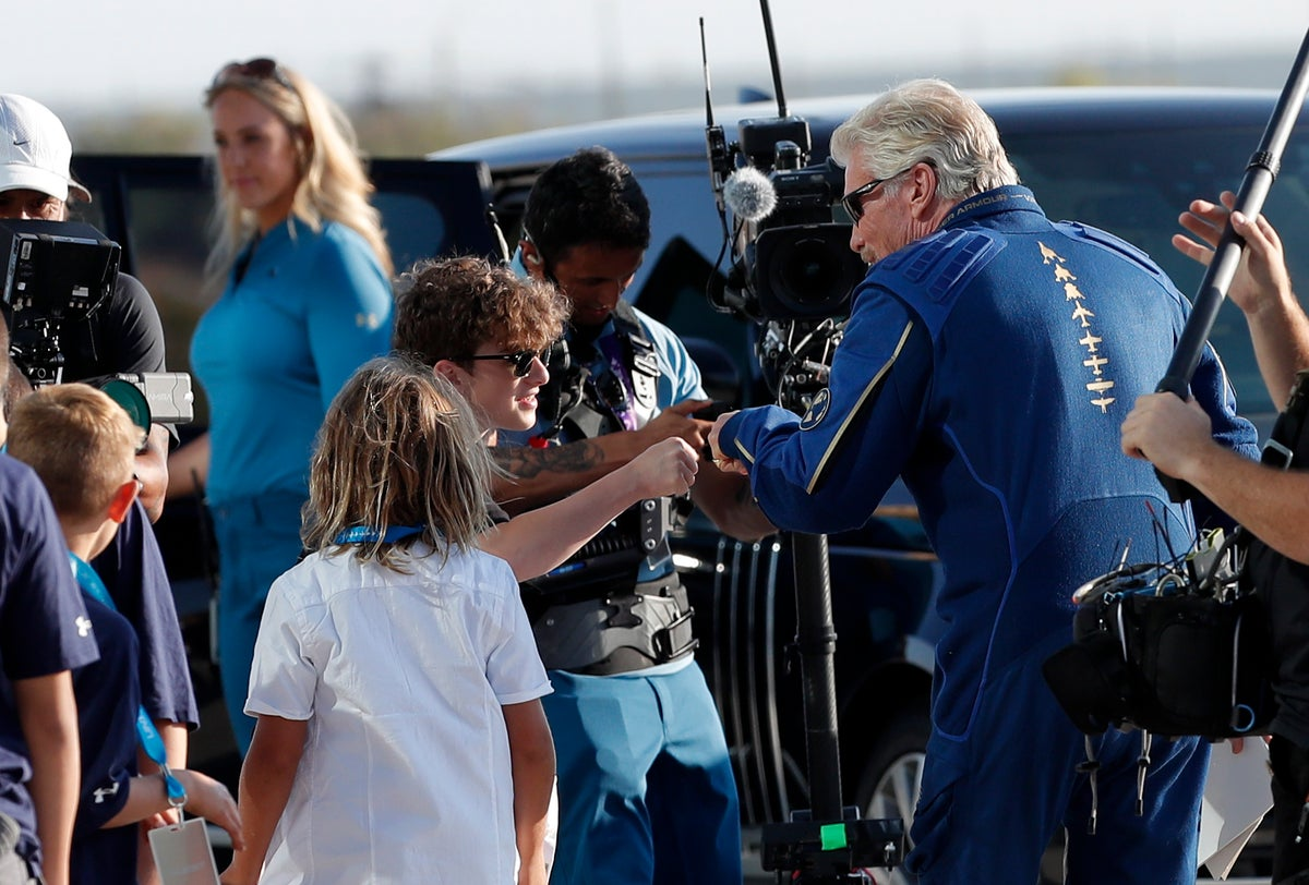 Virgin Galactic founder Richard Branson bump fists with a school boy before heading to board the rocket plane that flew him to the edge of space from Spaceport America near Truth or Consequences, New Mexico, Sunday, July 11, 2021. (AP Photo/Andres Leighton)
