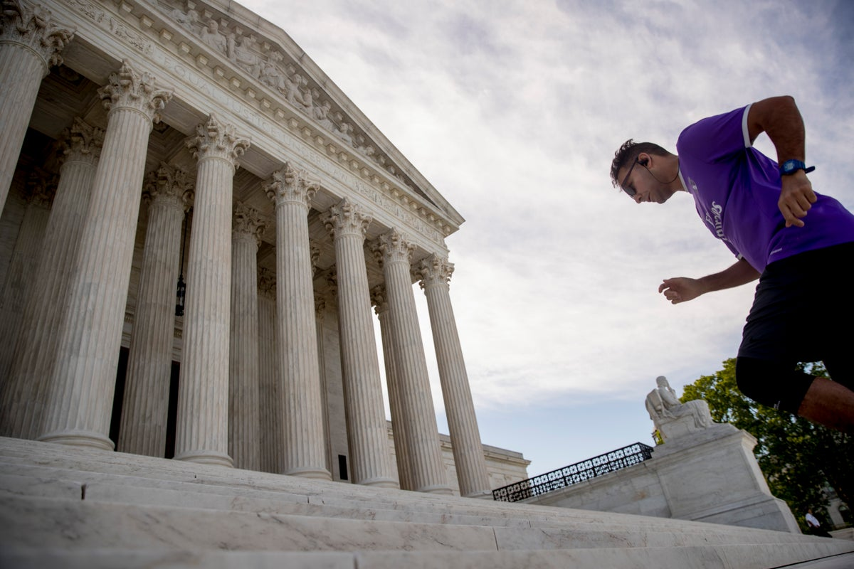 A man exercises on the steps of the Supreme Court where the justices will hold arguments by telephone for the first time ever, Monday, May 4, 2020, in Washington. (AP Photo/Andrew Harnik)