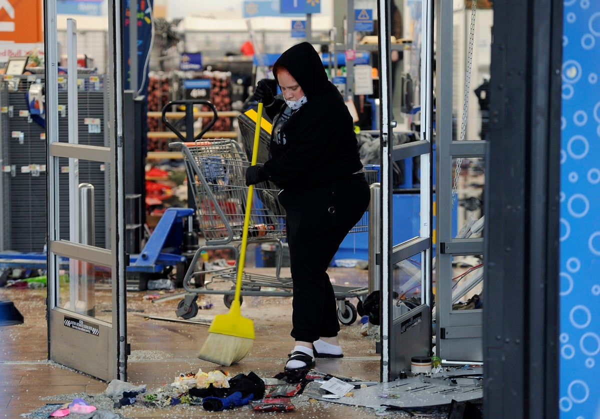 A woman cleans up debris at a Walmart, Wednesday, Oct. 28, 2020, that was damaged in protests in Philadelphia. (AP Photo/Michael Perez)