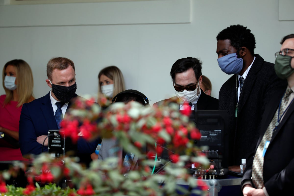 Staff members wear masks as they listen to President Donald Trump speak about the coronavirus during a press briefing in the Rose Garden of the White House, Monday, May 11, 2020, in Washington. (AP Photo/Alex Brand)