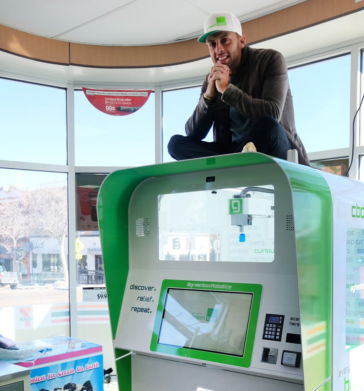 <i>Greenbox Robotics CEO and founder Zack Johnson poses with a robot in a Colorado 7-Eleven.  / Photo Credit: Caroline Murphy/Greenbox</i>