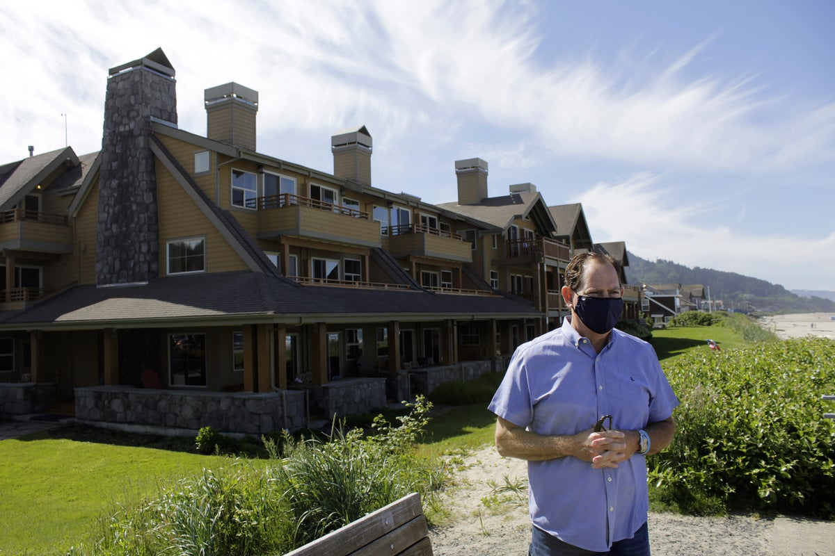 In this Thursday, May 28, 2020, photo, Patrick Nofield, whose company, Escape Lodging, owns and operates four hotels in Cannon Beach, Ore., stands in front of the flagship property, The Ocean Lodge, while wearing a face mask due to the novel coronavirus. (AP Photo/Gillian Flaccus)