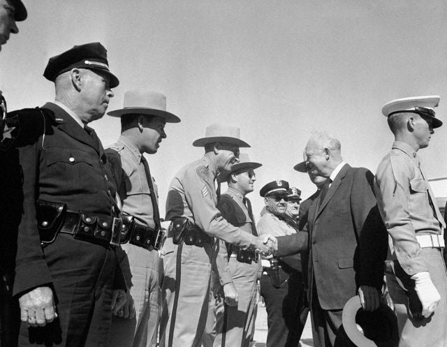 When President Dwight Eisenhower meeting Florida Highway Patrolman Slim Harvey in Key West, Florida on Jan. 7, 1956. The president concluded a ten-day vacation with a morning press conference, first since his illness. (AP Photo/Henry Griffin)
