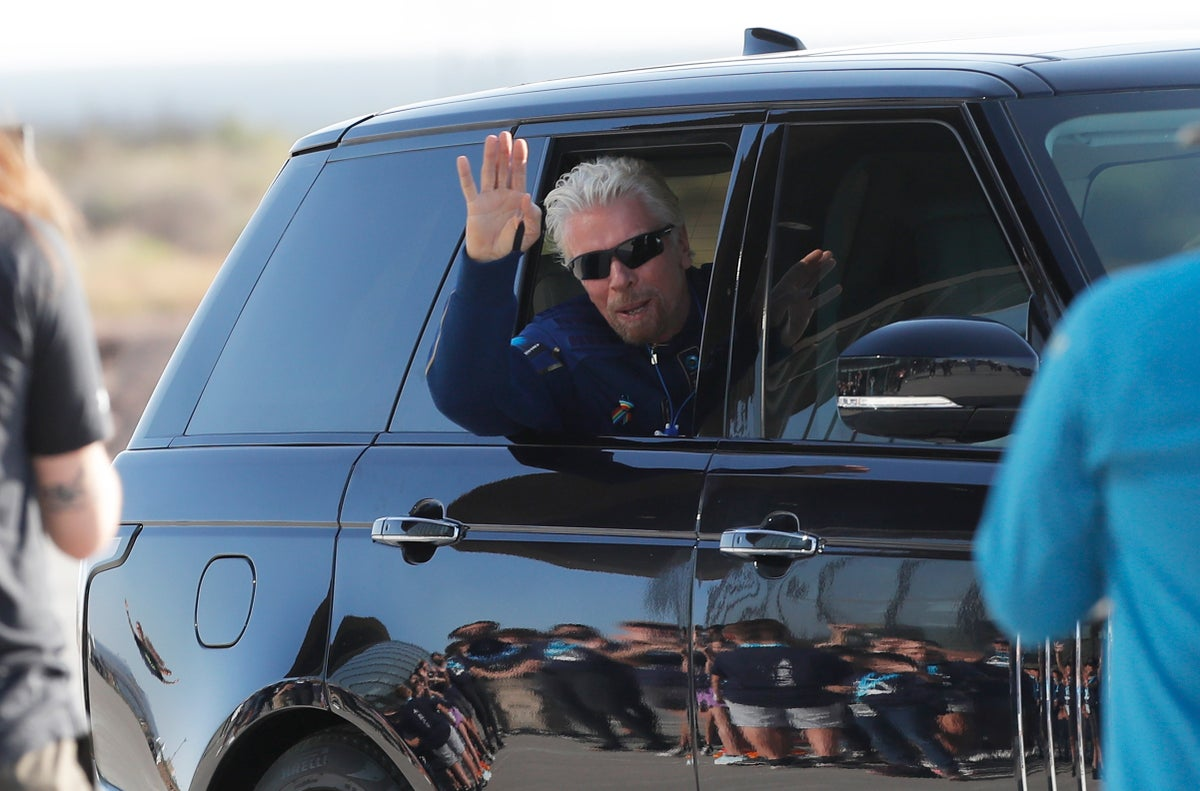 Virgin Galactic founder Richard Branson waves goodbye while heading to board the rocket plane that will flew him to space from Spaceport America near Truth or Consequences, New Mexico, Sunday, July 11, 2021. (AP Photo/Andres Leighton)
