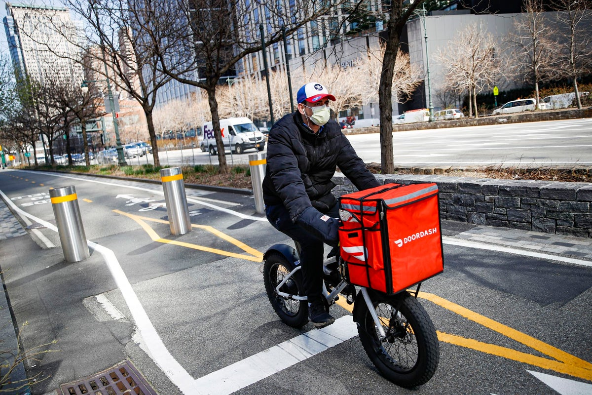 In this March 16, 2020 file photo, a delivery worker rides his bicycle along a path on the West Side Highway in New York. The pandemic shuffled the deck for the so-called gig economy as fear of contracting the coronavirus led many who once traveled in shared vehicles to stay home, and grocery delivery services struggled to keep up with demand from people who didn't want to risk stepping into a store. (AP Photo/John Minchillo, File)