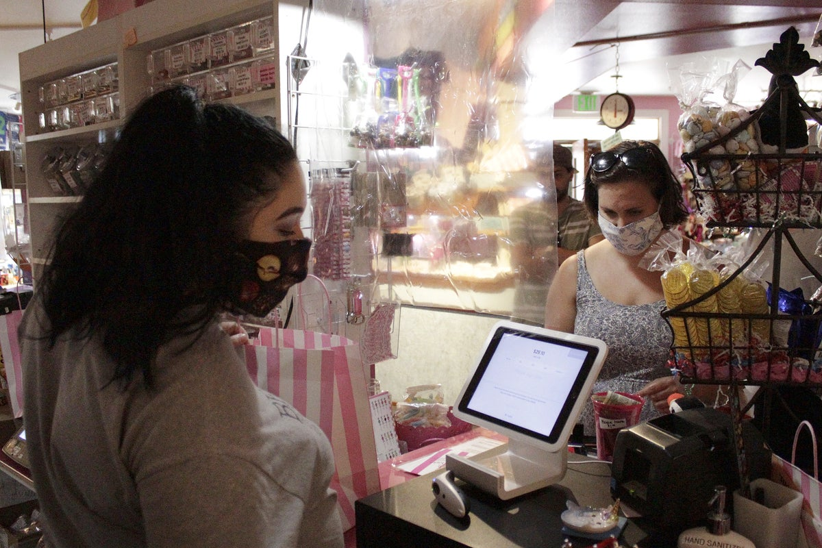 In this Thursday, May 28, 2020, photo, an employee at Bruce's Candy Kitchen ring up a customer's purchases from behind a protective plastic shield as both wear face masks due to the coronavirus in Cannon Beach, Ore. (AP Photo/Gillian Flaccus)