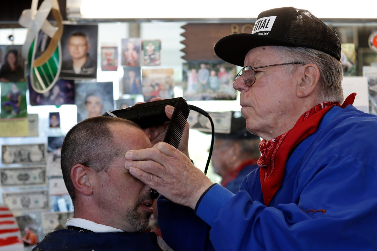 Barber Bob Martin, right, holds a hand over the eyes of customer Chad Buggey as he cuts his hair while keeping the shop open in defiance of the governor's stay-home orders during the coronavirus outbreak, Tuesday, May 5, 2020, in Snohomish, Wash.  (AP Photo/Elaine Thompson)