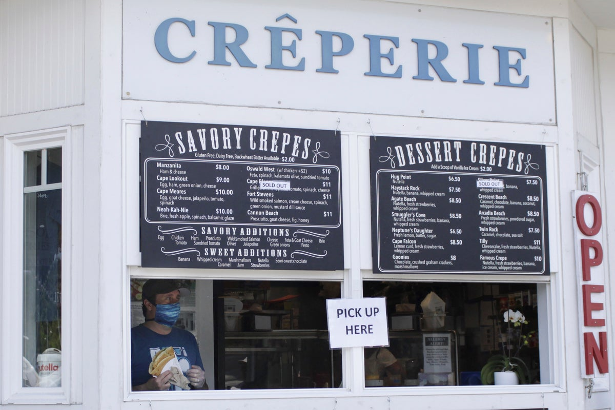 In this Thursday, May 28, 2020, photo, Yuri Vidal, co-owner of Crepe Neptune, wearing a face mask due to the coronavirus as he holds a customer's order at the take-out window of the creperie in Cannon Beach, Ore. (AP Photo/Gillian Flaccus)