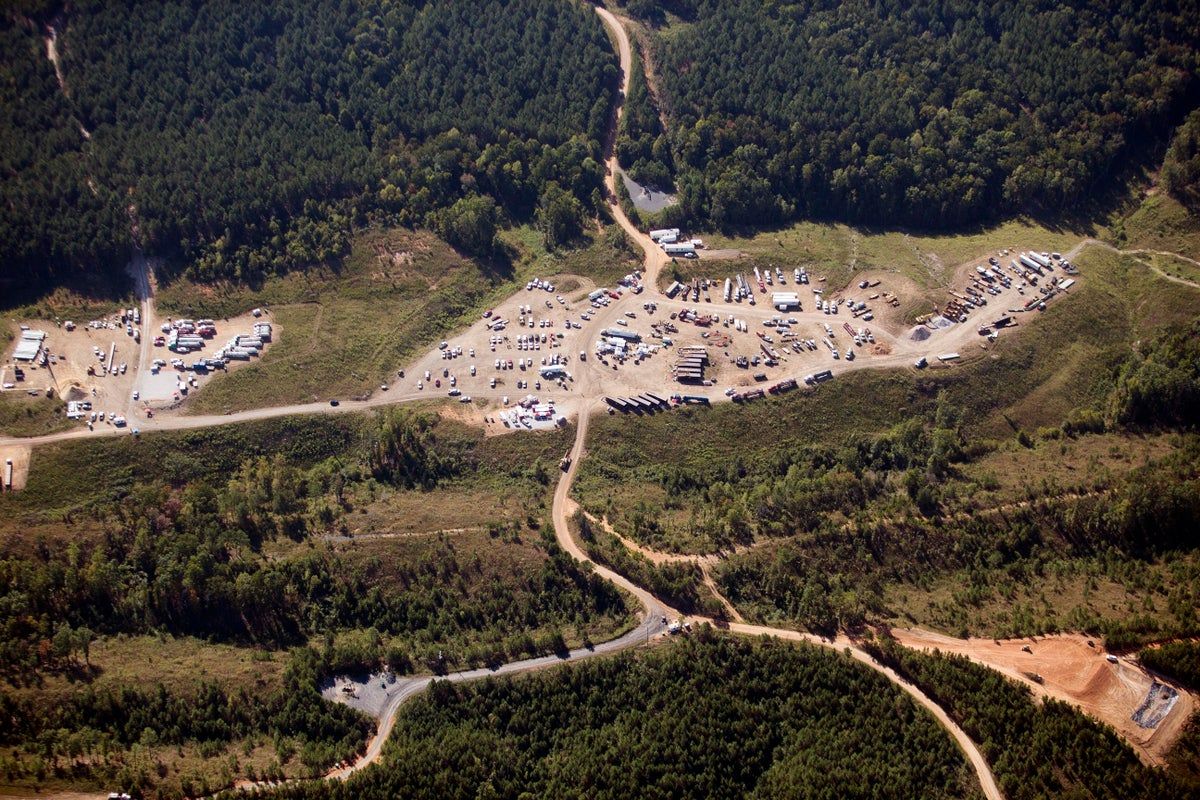 """In this Sept. 20, 2016 file photo vehicles are seen near Colonial Pipeline in Helena, Ala. A major pipeline that transports fuels along the East Coast says it had to stop operations because it was the victim of a cyberattack. Colonial Pipeline said in a statement late Friday that it """"took certain systems offline to contain the threat, which has temporarily halted all pipeline operations, and affected some of our IT systems."""" (AP Photo/Brynn Anderson, File)"""