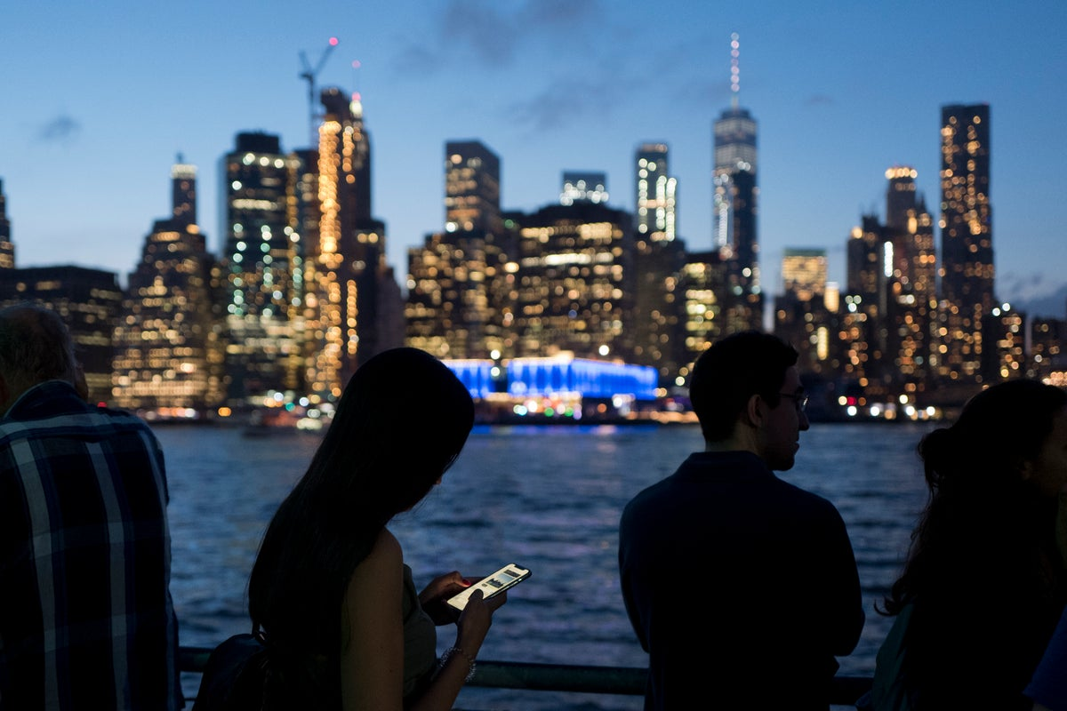 A woman standing in Brooklyn Bridge Park looks at her mobile phone, Oct. 10, 2018 in New York. Beyond her is the East River and the lower Manhattan skyline. (AP Photo/Mark Lennihan)