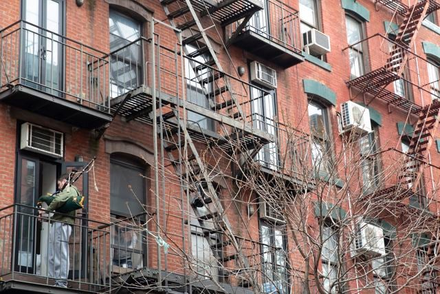 A man plays the bagpipe on his fire escape, Tuesday, March 17, 2020, in New York.(AP Photo/Mary Altaffer)