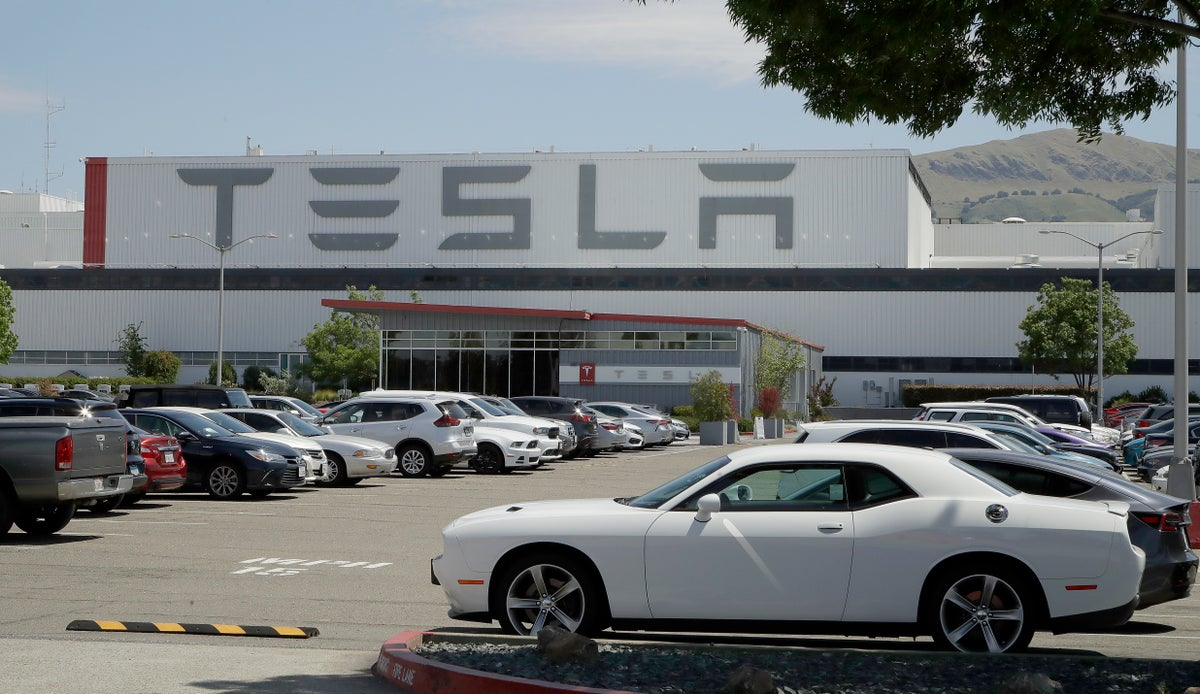 Vehicles are seen parked at the Tesla car plant Monday, May 11, 2020, in Fremont, Calif. The parking lot was nearly full at Tesla's California electric car factory Monday, an indication that the company could be resuming production in defiance of an order from county health authorities. (AP Photo/Ben Margot)