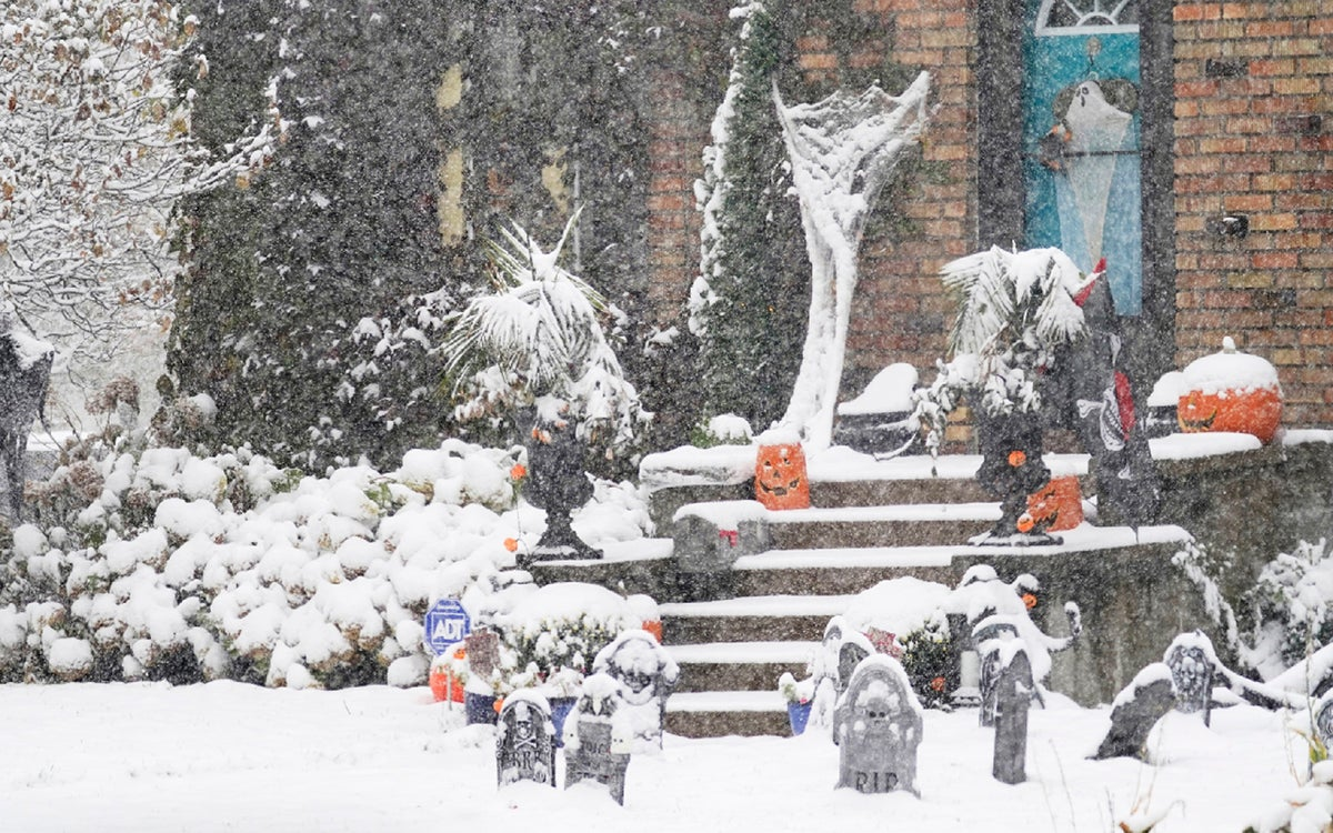 A Halloween display in Minneapolis receives the first measurable snow of the season as a storm arrived over much of Minnesota Tuesday, Oct. 20, 2020. (AP Photo/Jim Mone)