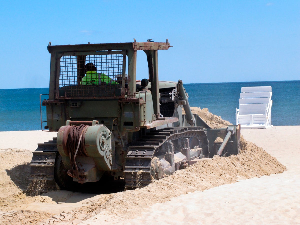 In this Tuesday, May 12, 2020 photo, workers prepare the beach in Belmar, N.J. for the summer season amid the coronavirus pandemic. Gov. Phil Murphy is expected to issue guidelines on Thursday, May 14, 2020, on when and how New Jersey's beaches can begin to reopen during the COVID-19 pandemic. (AP Photo/Wayne Parry)