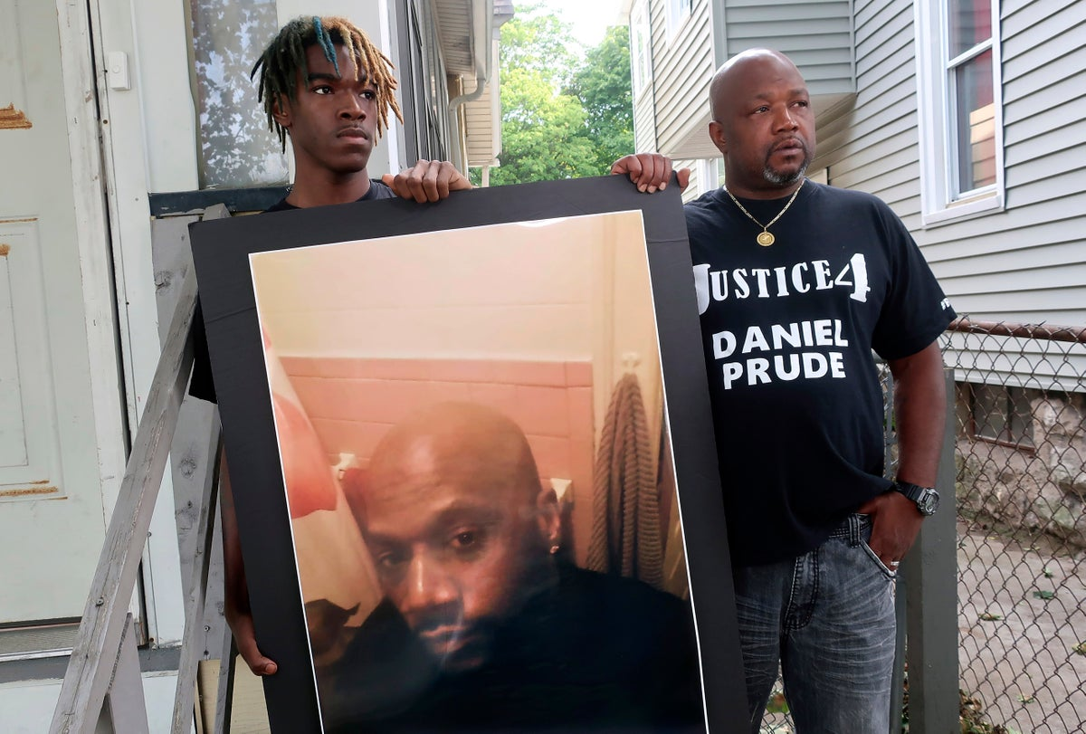 Joe Prude, right, uncle of Daniel Prude, and Daniel's nephew Armin, stand with a picture of Daniel Prude in Rochester, N.Y. (AP Photo/Ted Shaffrey, File)